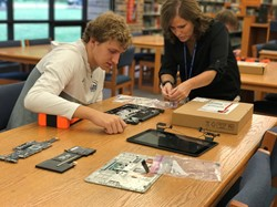 Tech Support Internship student Matt works with Mrs. O'Malley on a 1:1 device