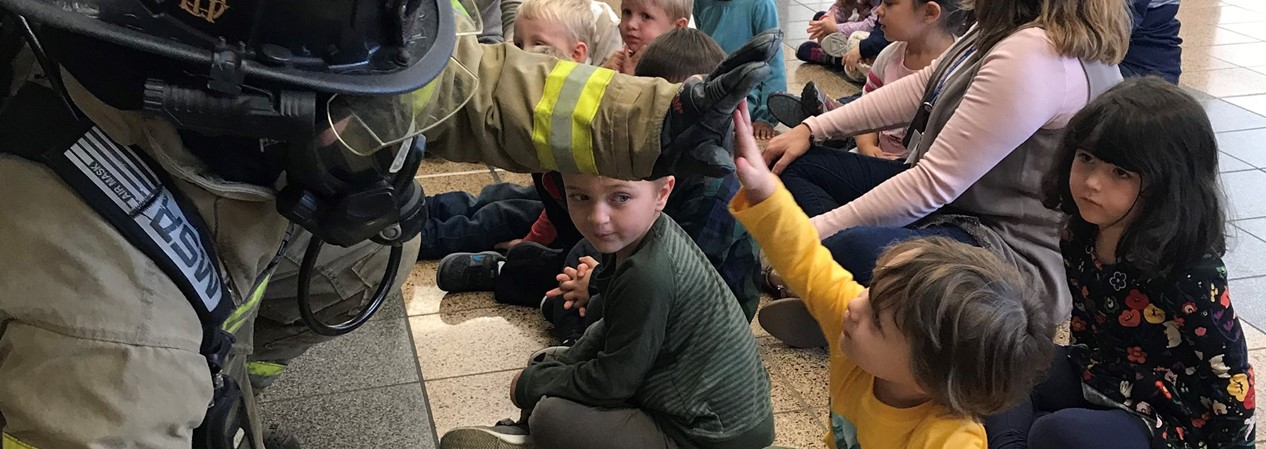 Early Learning students learn about firefighters and the suits that they wear.