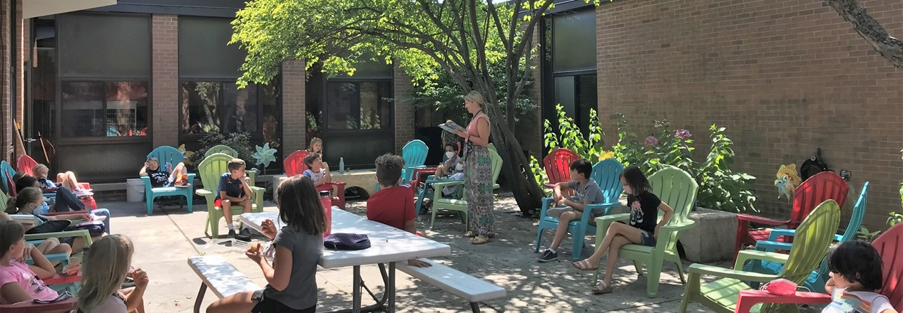 Teacher Reads to Students in Courtyard